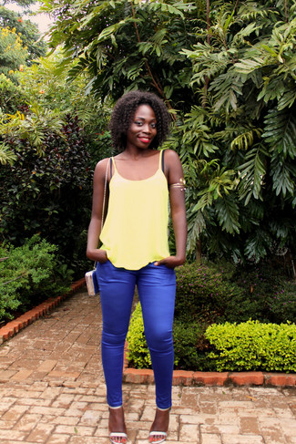 This pairing of a yellow tank and blue skinny pants is extremely versatile and really up for any sort of adventure you may find yourself on. Let's make a bit more effort now and rock a pair of silver leather heeled sandals. This getup is likely to become your hot weather go-to.