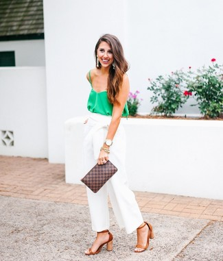 Team a green silk tank with white wide leg pants to effortlessly deal with whatever this day throws at you. Dress up this look with camel leather heeled sandals.