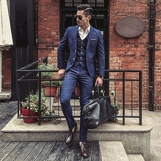 How to Wear a Black Leather Duffle Bag For Men: A navy three piece suit and a black leather duffle bag are a good go-to combination to have in your menswear collection. Bring an added touch of style to this look with dark brown leather tassel loafers.