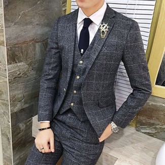 How to Wear a Lapel Pin: A charcoal check three piece suit and a lapel pin are bona fide menswear must-haves if you're figuring out a casual wardrobe that holds to the highest style standards.