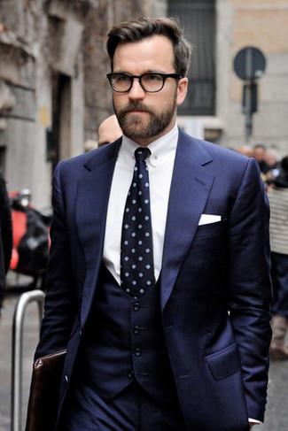 How to wear: navy three piece suit, white dress shirt, dark brown leather zip pouch, navy print tie