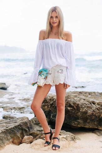 Cómo combinar: top con hombros descubiertos blanco, pantalones cortos de lino blancos, sandalias planas de cuero negras, cartera sobre de lona estampada blanca