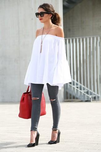 Cómo combinar: top con hombros descubiertos blanco, vaqueros pitillo desgastados en gris oscuro, sandalias con cuña de cuero negras, bolsa tote de cuero roja