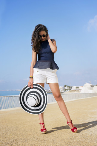 Cómo combinar: top con sobrefalda azul marino, pantalones cortos blancos, sandalias con cuña de ante rojas, sombrero de paja en blanco y negro