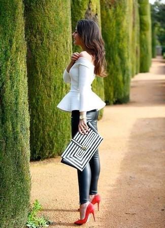 Cómo combinar: top con sobrefalda blanco, leggings de cuero negros, zapatos de tacón de ante rojos, cartera sobre de cuero con estampado geométrico en negro y blanco