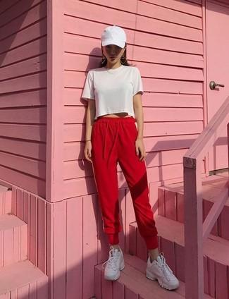 Cómo combinar: top corto blanco, pantalón de chándal rojo, tenis de cuero blancos, gorra inglesa blanca