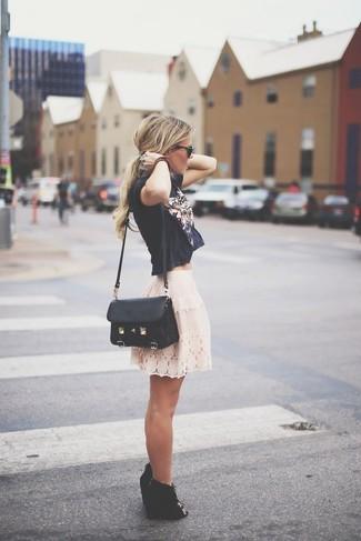 Cómo combinar: top corto estampado negro, falda skater de encaje en beige, botines con cuña de ante con recorte negros, bolso bandolera de cuero negro
