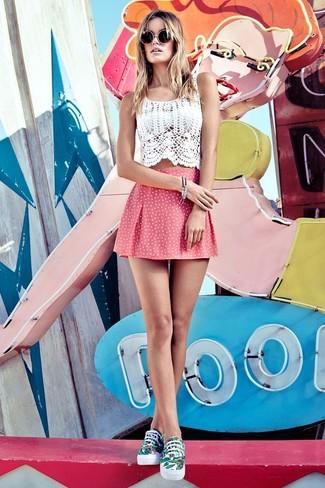 Para un atuendo tan cómodo como tu sillón utiliza un top corto de crochet blanco y una falda skater a lunares rosada. Completa el look con tenis en blanco y verde.