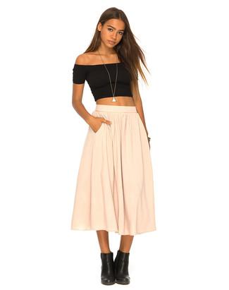 Cómo combinar: top corto negro, falda campana en beige, botines de cuero negros, colgante plateado