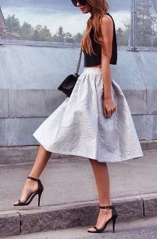 Ponte un top corto negro y una falda campana plateada para lidiar sin esfuerzo con lo que sea que te traiga el día. Dale un toque de elegancia a tu atuendo con un par de sandalias de tacón de cuero negras.
