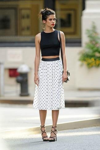 Cómo combinar: top corto negro, falda midi a lunares en blanco y negro, sandalias romanas de cuero negras, bolso bandolera de cuero negro