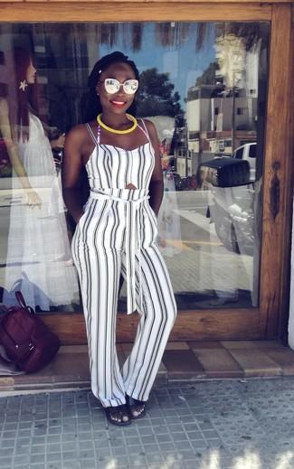 Cómo combinar: top corto de rayas verticales en blanco y negro, pantalón de pinzas de rayas verticales en blanco y negro, sandalias planas de cuero negras, gafas de sol doradas