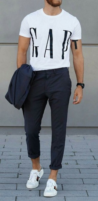 Cómo combinar: traje azul marino, camiseta con cuello circular estampada en blanco y negro, tenis de cuero blancos, reloj negro