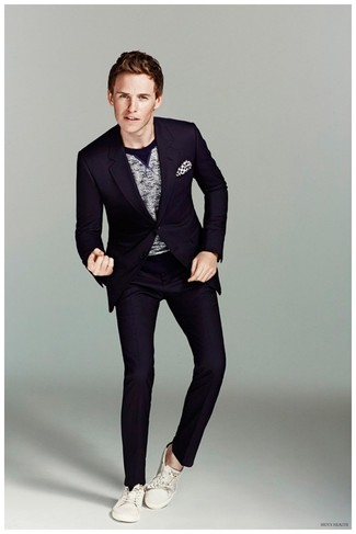 Cómo combinar: traje azul marino, jersey con cuello circular gris, tenis de lona blancos, pañuelo de bolsillo a lunares en blanco y negro