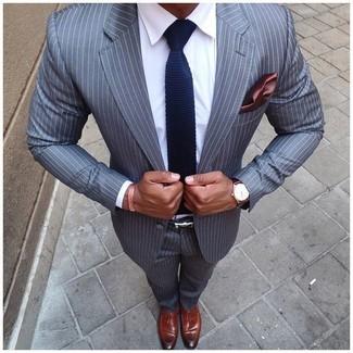 Cómo combinar: traje de rayas verticales gris, camisa de vestir blanca, mocasín con borlas de cuero marrón, corbata de punto azul marino