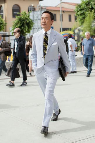 Cómo combinar: traje de seersucker celeste, camisa de vestir blanca, mocasín con borlas de cuero negro, portafolio de cuero negro