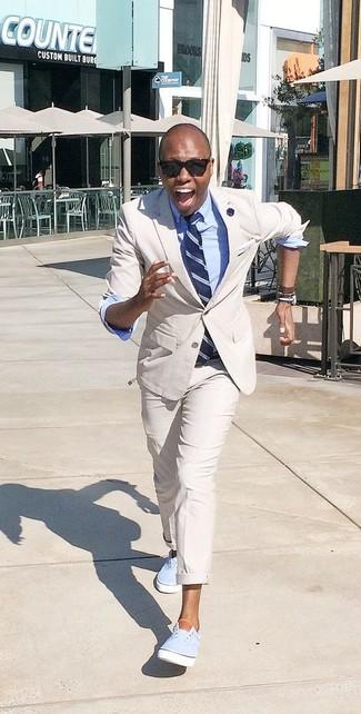Cómo combinar: traje en beige, camisa de vestir celeste, zapatillas plimsoll celestes, corbata de rayas verticales azul