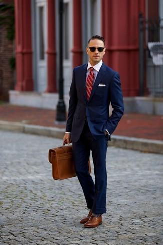 Cómo combinar: traje azul marino, camisa de vestir blanca, zapatos brogue de cuero marrónes, portafolio de cuero marrón