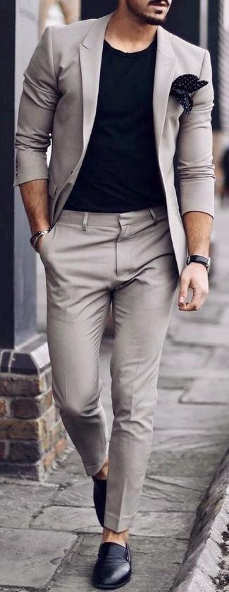 Cómo combinar: traje gris, camiseta con cuello circular negra, zapatillas slip-on de cuero negras, pañuelo de bolsillo a lunares en negro y blanco