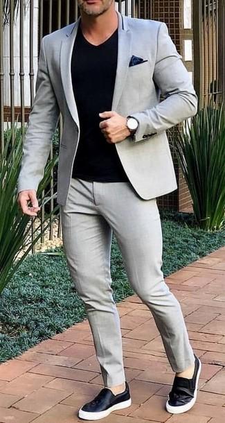 Cómo combinar: traje gris, camiseta con cuello en v negra, zapatillas slip-on de cuero negras, pañuelo de bolsillo de seda negro