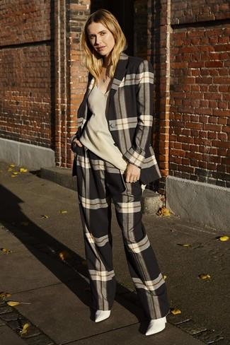 Cómo combinar: traje de tartán en negro y blanco, blusa sin mangas de seda en beige, botines de cuero blancos