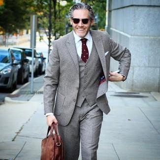Cómo combinar: traje de tres piezas a cuadros gris, camisa de vestir blanca, portafolio de cuero marrón, corbata estampada burdeos