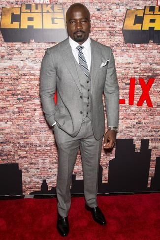 Cómo combinar: traje de tres piezas de lana gris, camisa de vestir blanca, zapatos con doble hebilla de cuero negros, corbata de rayas verticales gris