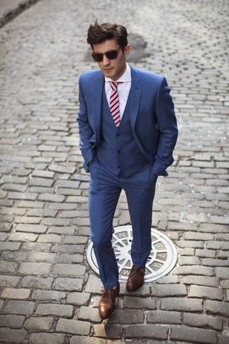 Cómo combinar: traje de tres piezas azul, camisa de vestir blanca, zapatos con doble hebilla de cuero marrónes, corbata de rayas verticales roja