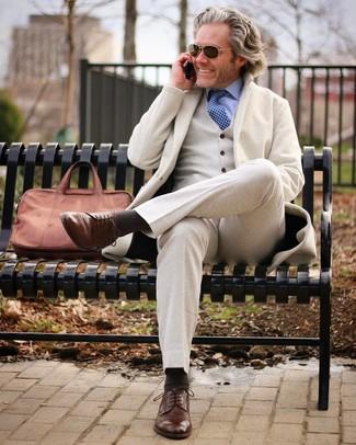 Cómo combinar: traje de tres piezas de lana en beige, camisa de vestir celeste, zapatos derby de cuero marrónes, portafolio de cuero marrón