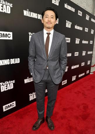 Cómo combinar: traje en gris oscuro, camisa de vestir blanca, zapatos derby de cuero en marrón oscuro, corbata en marrón oscuro