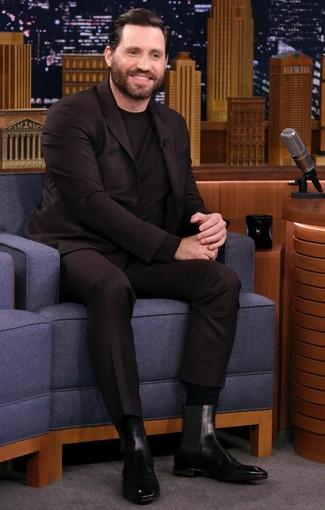 Cómo combinar: traje en marrón oscuro, jersey con cuello circular negro, botines chelsea de cuero negros, calcetines negros