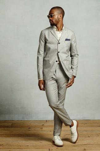 Cómo combinar: traje gris, camisa de vestir de tartán en beige, zapatos derby de ante blancos, pañuelo de bolsillo estampado azul marino