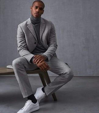 Cómo combinar: traje de lana gris, jersey de cuello alto gris, tenis de cuero blancos, calcetines negros