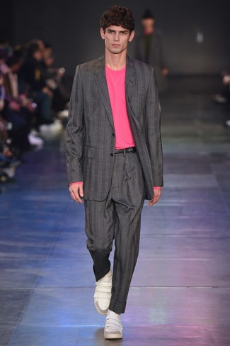 Cómo combinar: traje de rayas verticales gris, jersey con cuello circular rosa, tenis de cuero blancos, correa de cuero negra