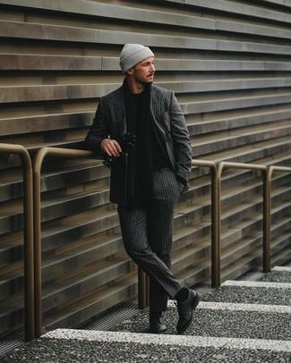 Cómo combinar: traje de rayas verticales en gris oscuro, jersey con cuello circular negro, zapatos derby de cuero negros, gorro gris