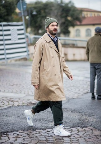How to Wear a Tan Trenchcoat For Men: If the situation calls for a polished yet cool getup, you can dress in a tan trenchcoat and dark green chinos. Introduce a pair of white leather high top sneakers to the equation to instantly amp up the street cred of your getup.