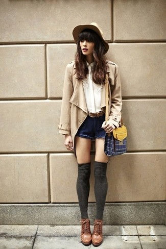 How to wear: tan trenchcoat, white silk button down blouse, navy denim shorts, brown leather lace-up ankle boots