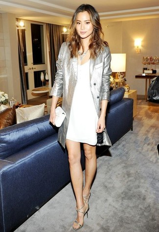 A silver trenchcoat with a white cami dress has become an essential combination for many style-conscious girls. Silver leather heeled sandals will add a touch of polish to an otherwise low-key look. A great illustration of transitional style, this outfit is a staple come warmer days.