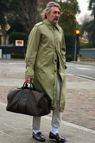 How to Wear a Dark Brown Print Leather Holdall For Men: Pairing an olive trenchcoat with a dark brown print leather holdall is an amazing choice for a cool and casual look. A trendy pair of burgundy leather loafers is a simple way to transform this getup.