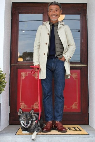 How to wear: beige trenchcoat, olive gilet, navy crew-neck sweater, navy jeans