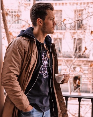 How to wear: brown trenchcoat, black hoodie, black print crew-neck t-shirt, blue jeans