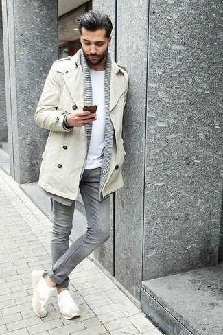 How to Wear White Athletic Shoes For Men: This combination of a beige trenchcoat and grey jeans is an interesting balance between dressy and casual. If you want to immediately tone down your ensemble with footwear, complete this outfit with a pair of white athletic shoes.