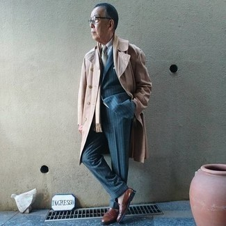 Beige Trenchcoat with Brown Leather Loafers Outfits For Men: Consider wearing a beige trenchcoat and a blue vertical striped suit for polished style with a modern spin. When it comes to shoes, introduce a pair of brown leather loafers to the mix.