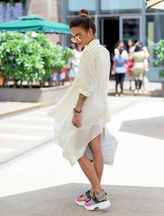 Cómo combinar: túnica de lino blanca, pantalones cortos blancos, sandalias planas de cuero en multicolor, gafas de sol doradas