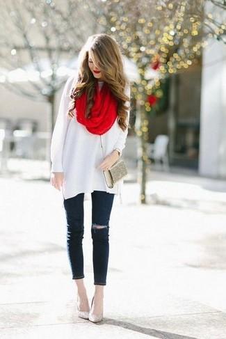 Cómo combinar: túnica de lana blanca, vaqueros pitillo desgastados negros, zapatos de tacón de lentejuelas dorados, cartera sobre dorada