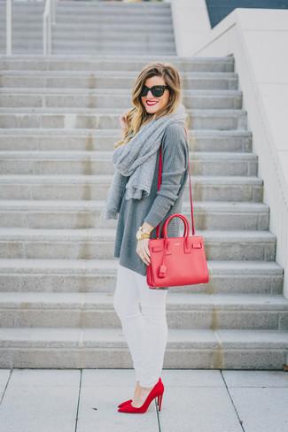 Cómo combinar: túnica de punto gris, vaqueros pitillo blancos, zapatos de tacón de ante rojos, bolso bandolera de cuero rojo