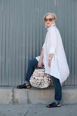Cómo combinar: túnica de lino blanca, vaqueros azul marino, sandalias planas de cuero negras, bolsa tote de lona bordada blanca