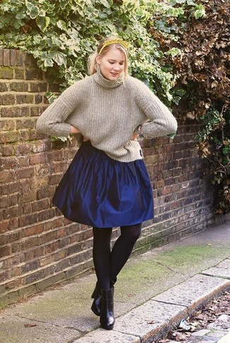 Step up your off-duty look in a grey knit turtleneck and a navy full skirt. Black leather ankle boots are a savvy choice to complete the look.