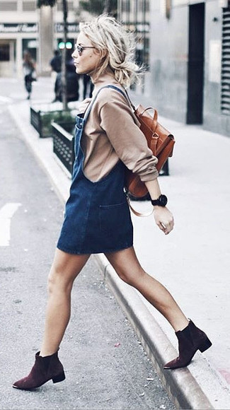 How to wear: beige turtleneck, navy denim overall dress, dark brown suede ankle boots, tobacco leather backpack