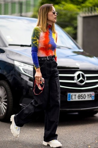 How to wear: multi colored tie-dye turtleneck, black denim wide leg pants, beige athletic shoes, black leather belt